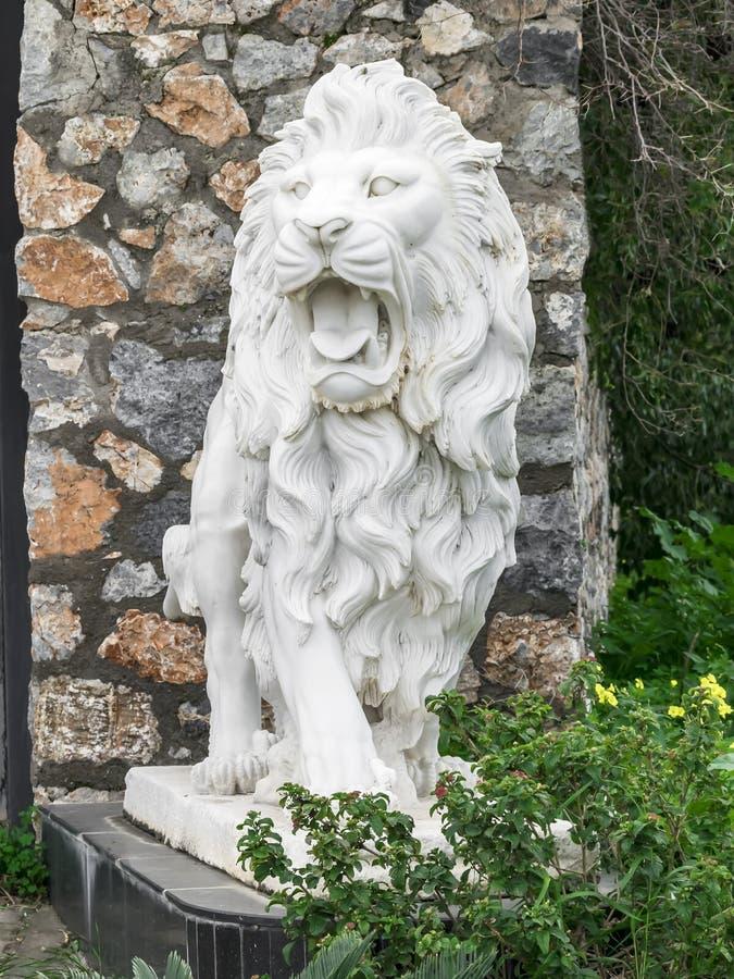 Escultura de la ciudad de un león blanco con la boca abierta en la entrada Señal local Front View fotos de archivo