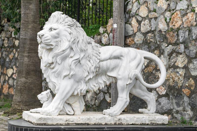 Escultura de la ciudad de un león y de un cachorro de león en la entrada Señal local Vista lateral fotografía de archivo