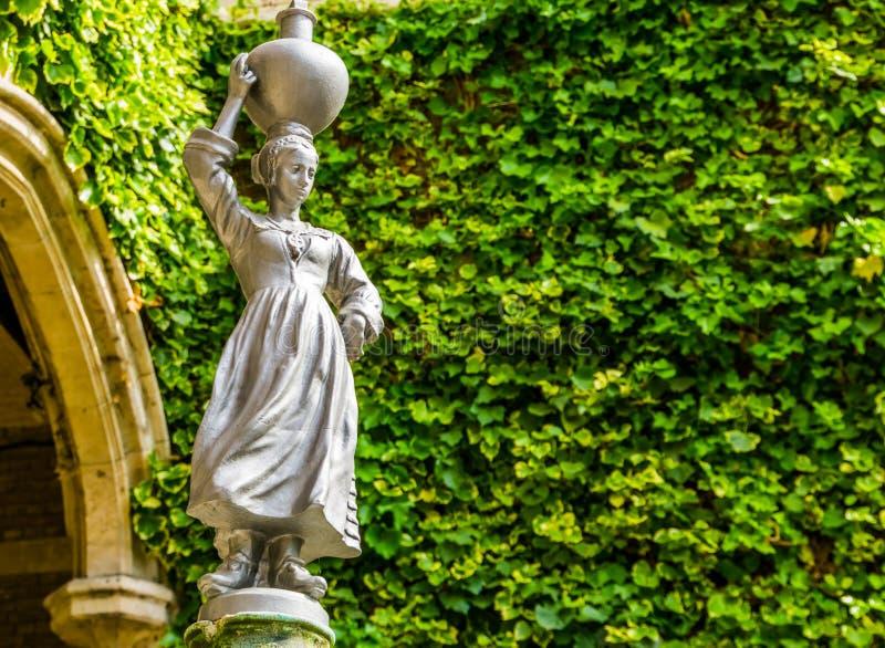Escultura de las mujeres que recogen el agua en una urna y que la llevan en su cabeza, decoraciones africanas del jardín y arquit imagen de archivo