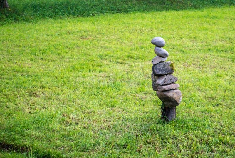 Escultura de las piedras en hierba imagenes de archivo
