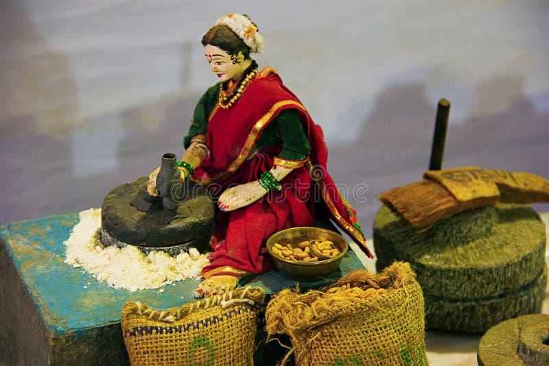 Escultura de los granos de pulido del trigo de la mujer tradicional de Maharashtrian fotos de archivo libres de regalías
