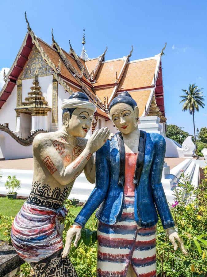 Escultura de los pares de amantes birmanos de una manera susurrante con el templo budista famoso de Wat Phumin en el fondo en la  fotografía de archivo