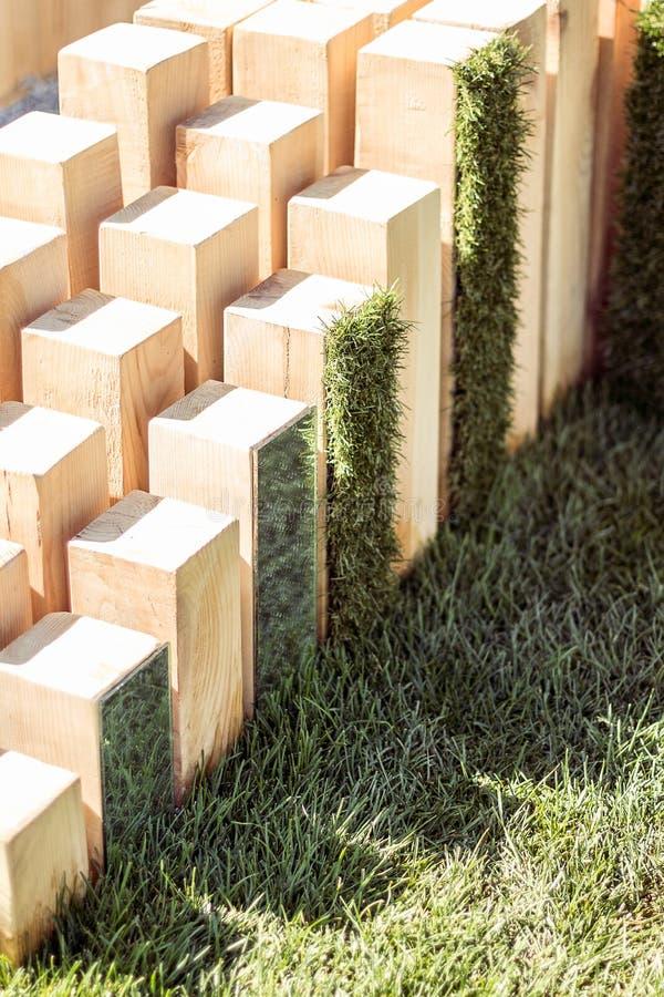 Escultura de madeira com os espelhos no fundo da grama no projeto do jardim fotografia de stock