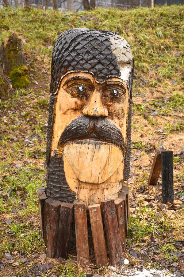 Escultura de madera en el parque bajo la forma de cara masculina con un bigote fotos de archivo