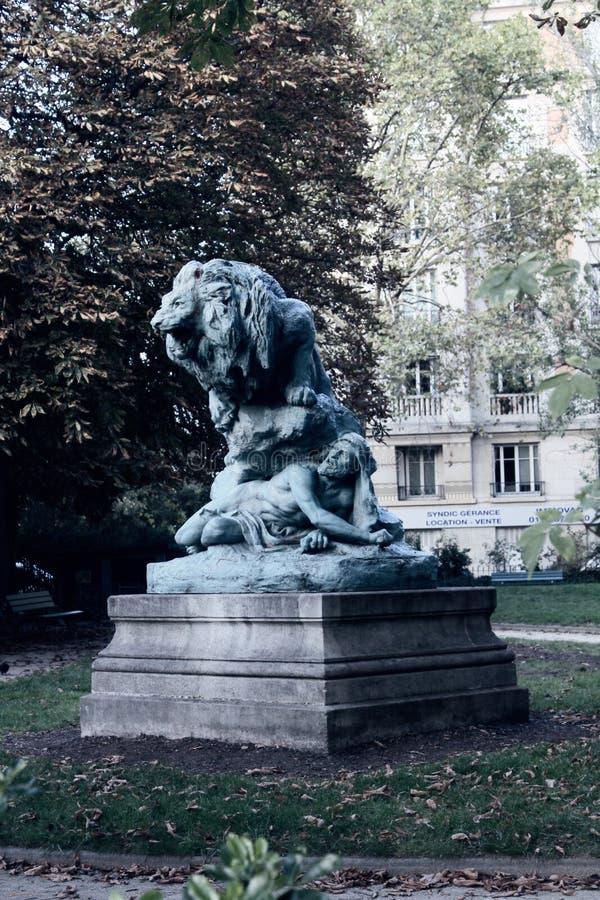 Escultura de Paris do homem que esconde do leão irritado sob a rocha foto de stock