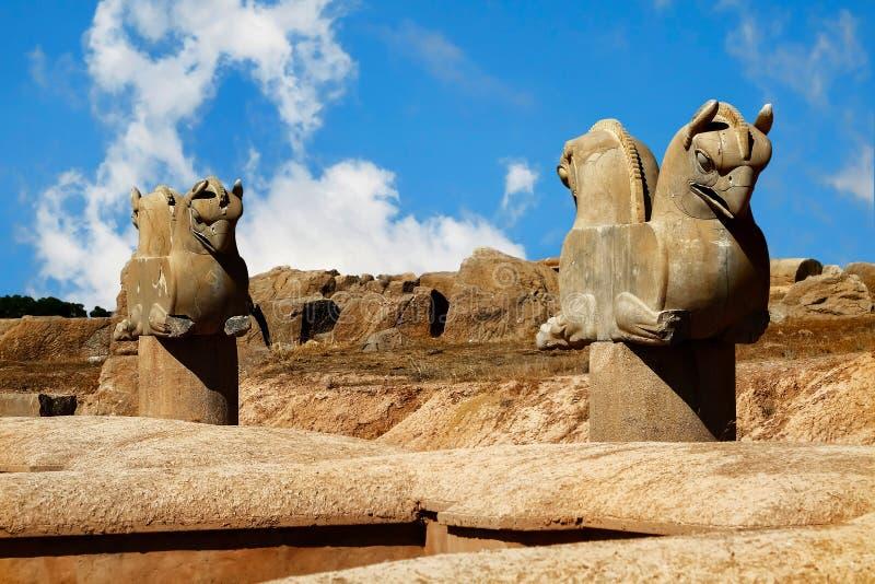 Escultura de pedra da coluna de um grifo em Persepolis contra um céu azul com nuvens O símbolo da vitória dos parentes antigos do imagem de stock