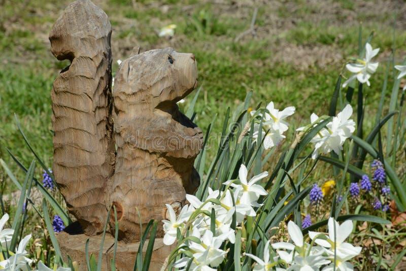 Escultura de Squirrell com flores fotografia de stock royalty free