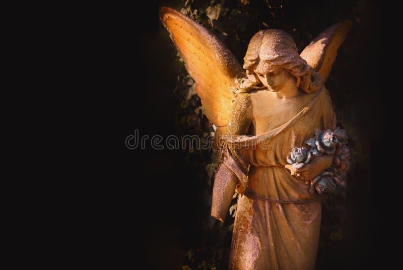 Escultura de um anjo com fundo escuro fotos de stock royalty free
