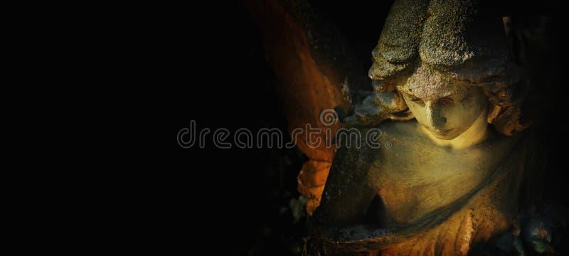 Escultura de um anjo com fundo escuro imagem de stock royalty free