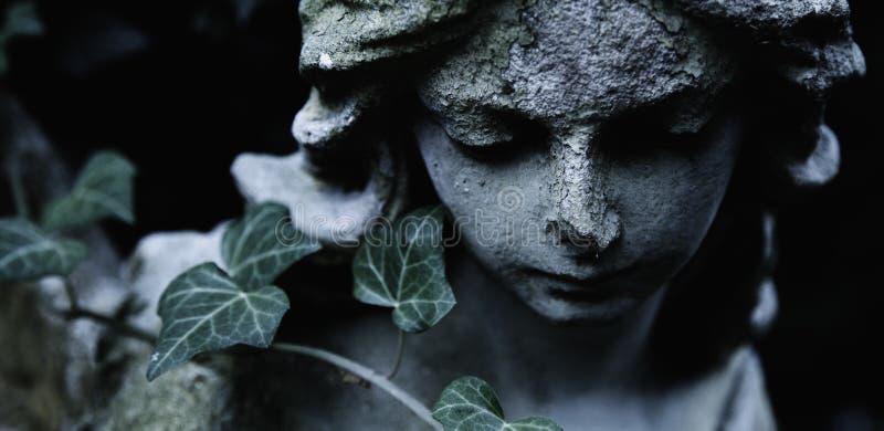 Escultura de um anjo com fundo escuro Estátua antiga foto de stock