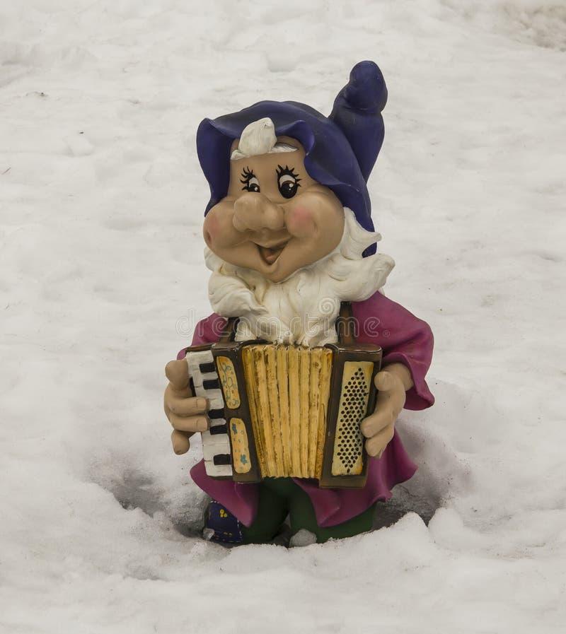 Escultura de um gnomo pequeno com um acordeão fotografia de stock royalty free