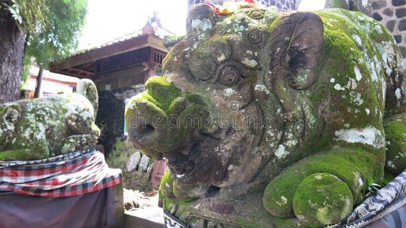 Escultura de um porco cinzelado da pedra natural Suporte envolvido com tela com teste padrão quadriculado Ilustração do mythol do foto de stock
