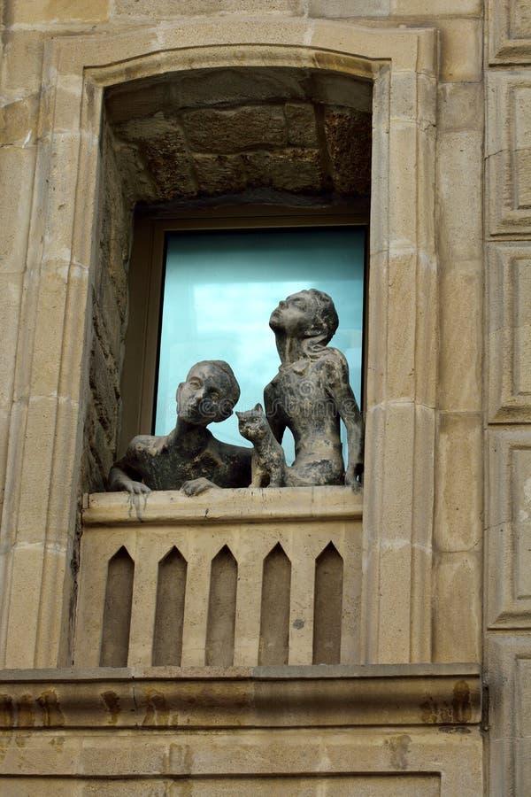 Escultura de uma menina, de um menino e de um gato olhando fora de uma janela no quarto velho da cidade de Baku imagens de stock