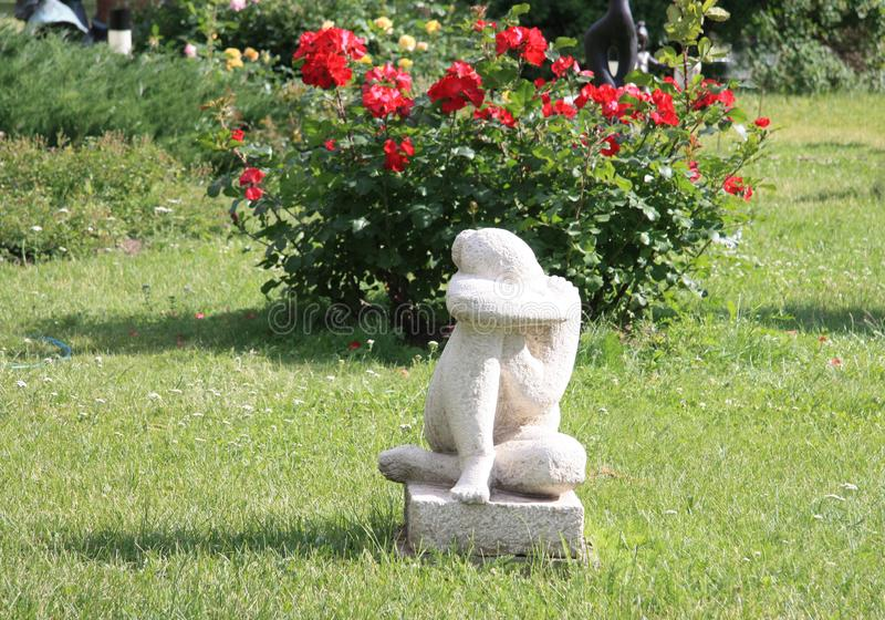 Escultura de uma menina triste em um jardim bonito fotos de stock royalty free
