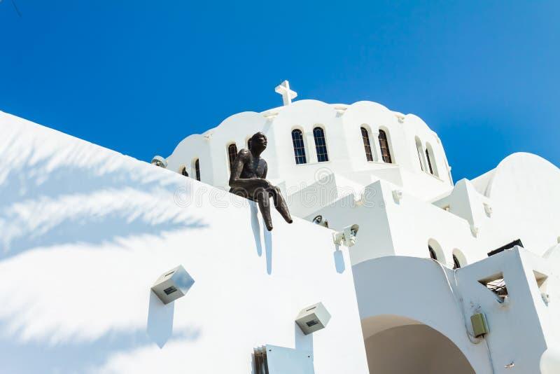 Escultura de un hombre que se sienta en el tejado de la catedral metropolitana ortodoxa de Ypapanti en el pueblo de Fira imagen de archivo