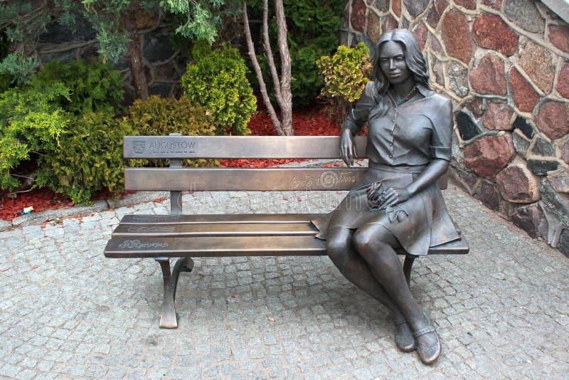 Escultura de una muchacha con la flor en Augustow, Polonia imagen de archivo