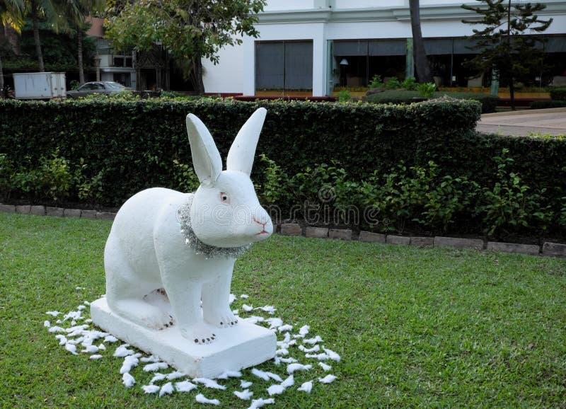 Escultura decorativa de un conejo, conejo blanco en un césped verde, decoración festiva del jardín imagen de archivo libre de regalías