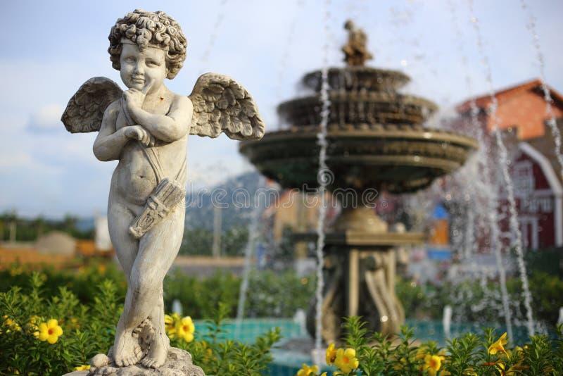 Escultura del ángel del bebé con una fuente fotos de archivo