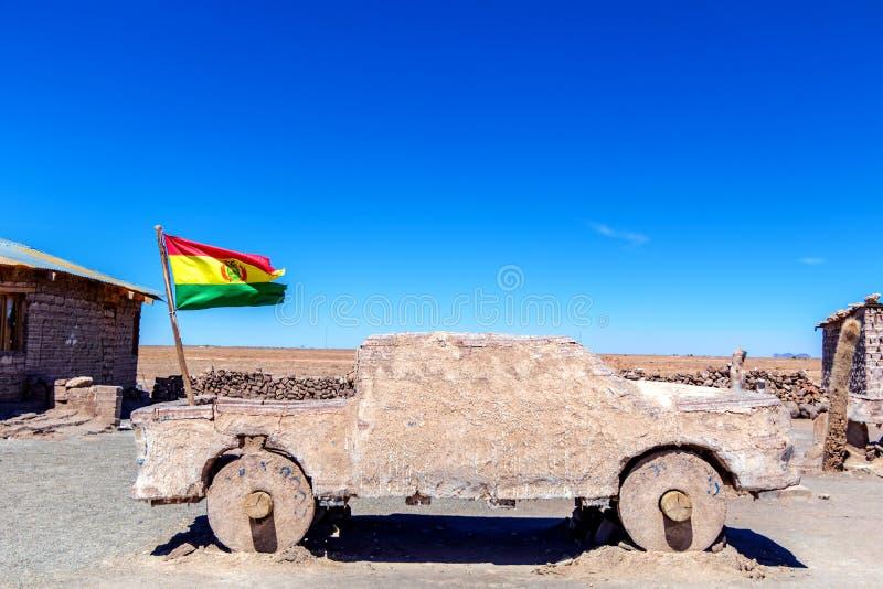 Escultura del coche y bandera boliviana en la sal Salar de Uyuni plano, Bolivia foto de archivo libre de regalías