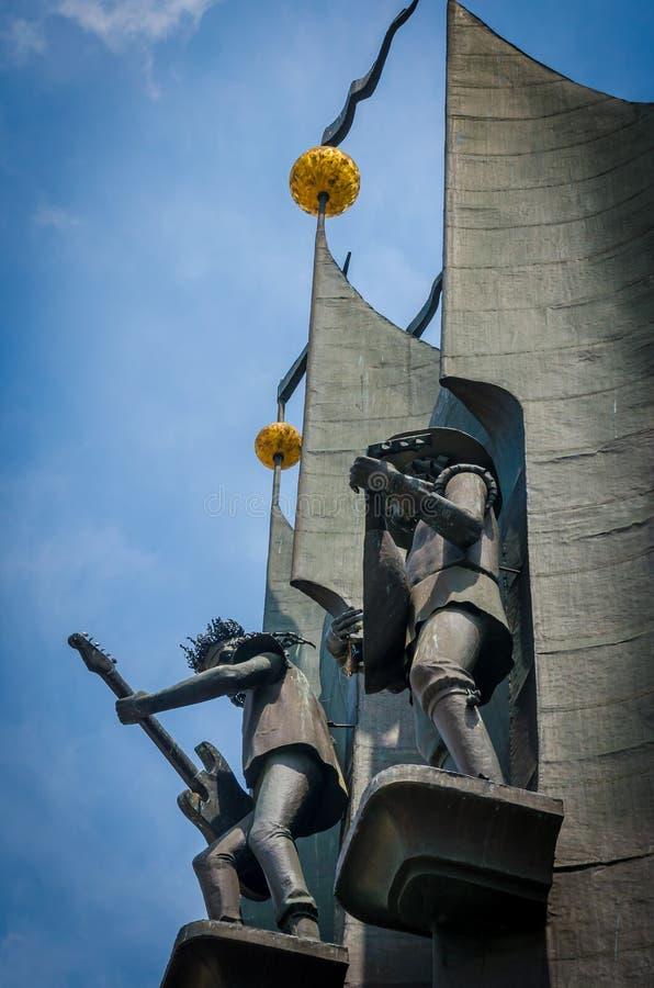 Escultura del hierro de los músicos de Bremen que tocan los instrumentos atados La foto los capturó de debajo, contra el contexto fotografía de archivo