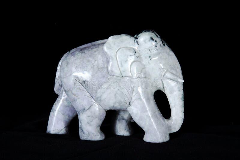 Escultura del jade del elefante aislada en fondo negro imagenes de archivo