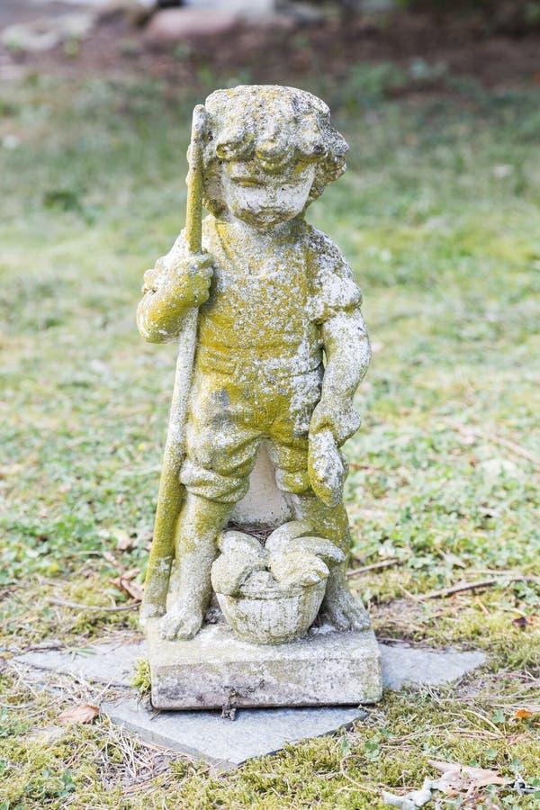 Escultura del muchacho que sostiene pescados y la caña de pescar en su mano fotos de archivo libres de regalías
