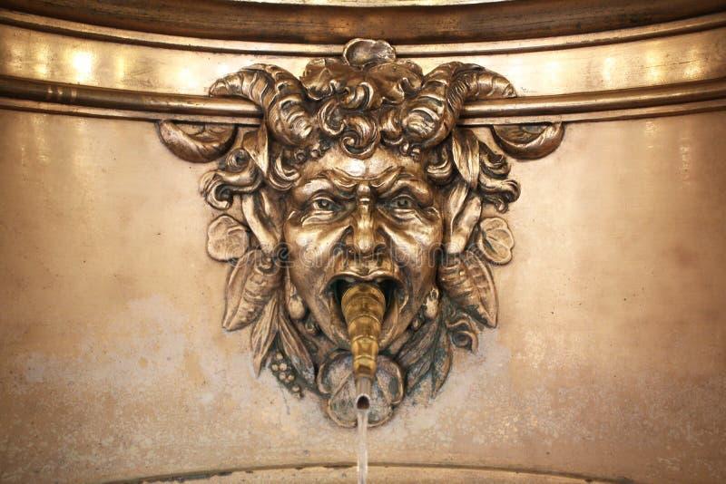 Escultura del rostro humano del agua potable de la calle antigua media de la fuente cabra de bronce del mito de la media en la ig fotos de archivo libres de regalías