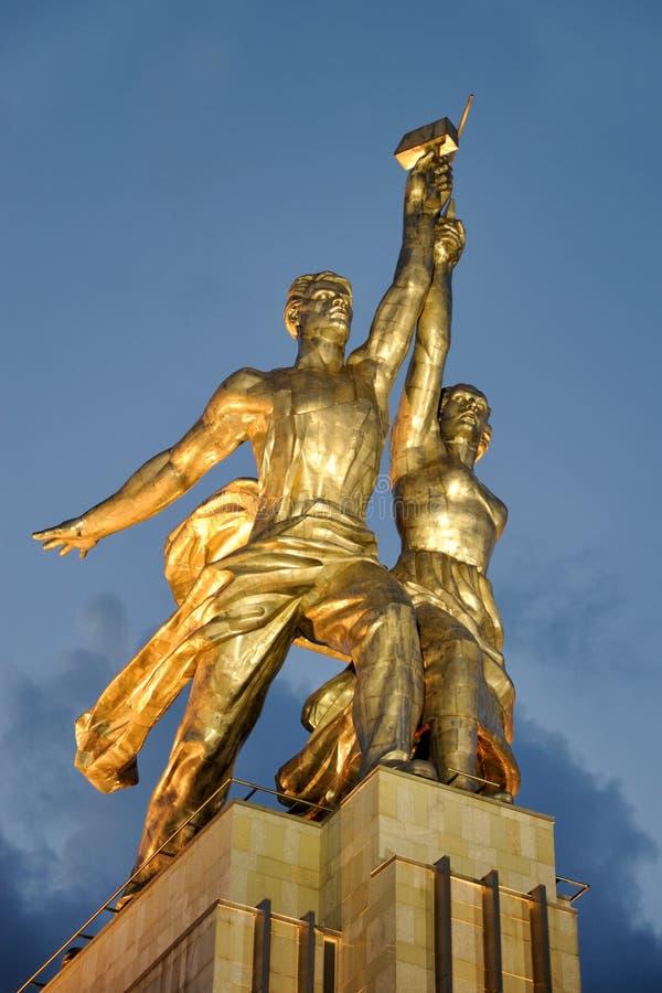 Escultura del trabajador y del granjero colectivo en luz del oro foto de archivo libre de regalías
