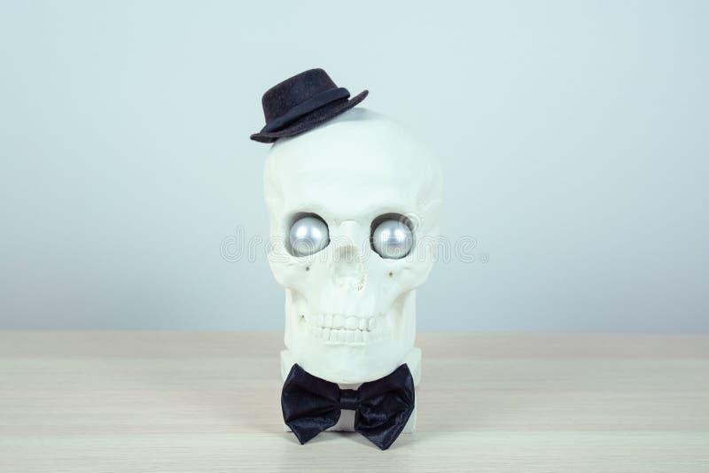 Escultura do crânio com chapéu negro e um laço preto Conceito do fundo do feriado Espaço livre para o projeto imagem de stock royalty free