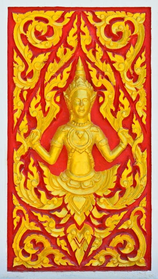 Escultura dourada do anjo na parede tailandesa do templo fotografia de stock royalty free