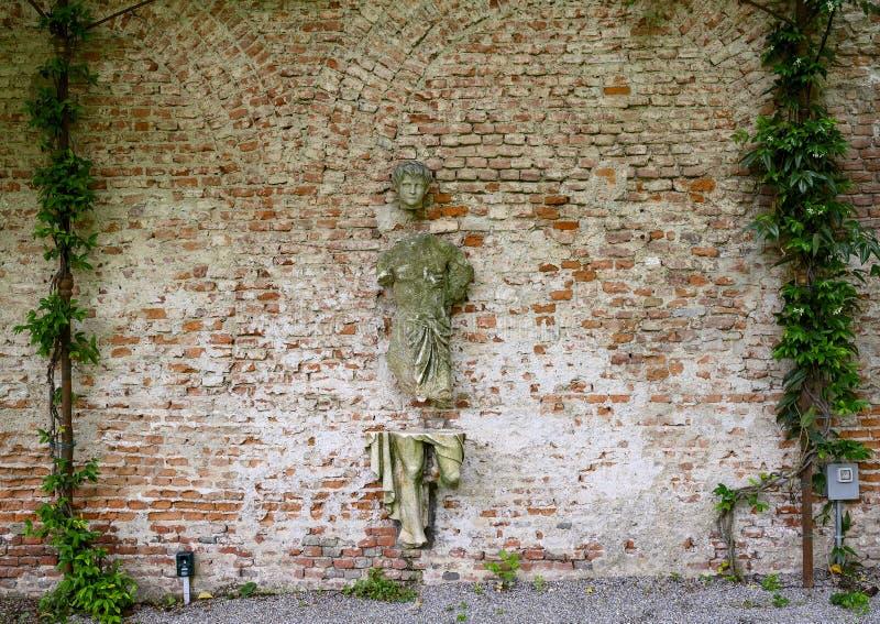 Escultura em uma parede de tijolo no jardim da casa de Atellani, Museo Vigna di Leonardo, Milão imagens de stock