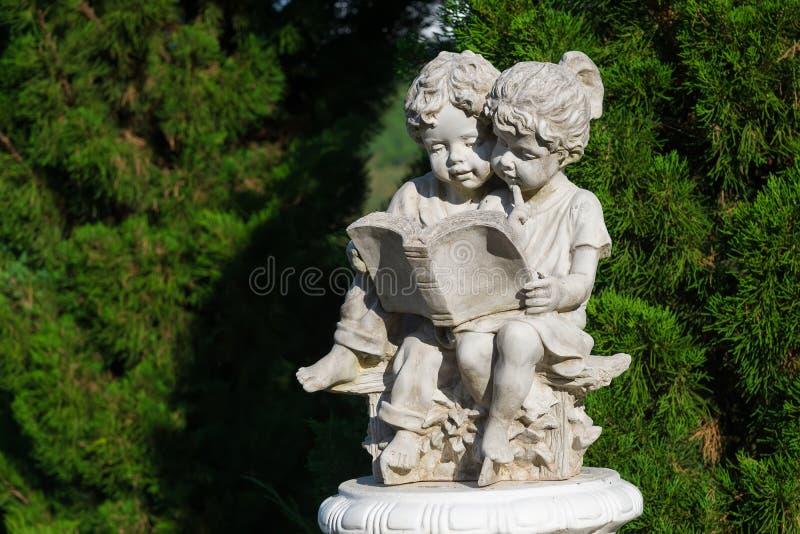 Escultura hermosa del libro de lectura del muchacho y de la muchacha fotografía de archivo