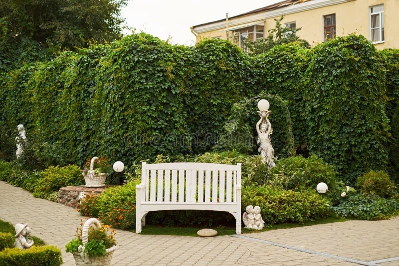 Escultura inglesa sola del ángel del fondo del verde del banco del jardín fotografía de archivo libre de regalías