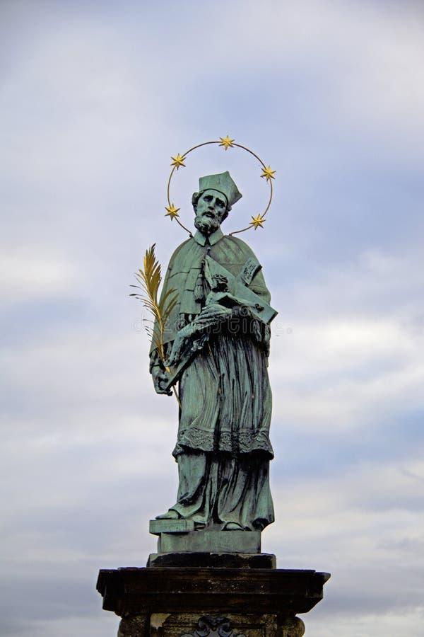 A escultura a mais velha da estátua em Charles Bridge em Praga que descreve St John de Nepomuk fotografia de stock royalty free