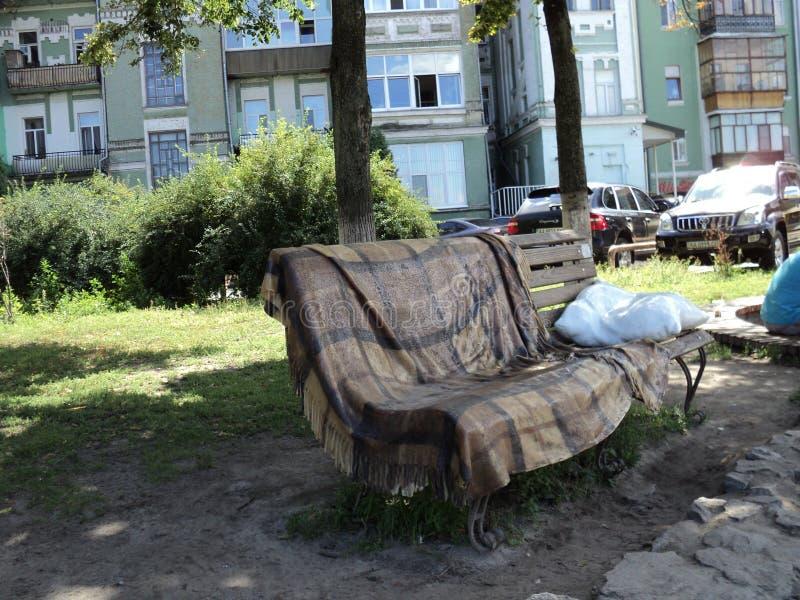 escultura original no parque da cidade sob a forma de um banco e um descanso e coberturas que encontram-se nele foto de stock royalty free
