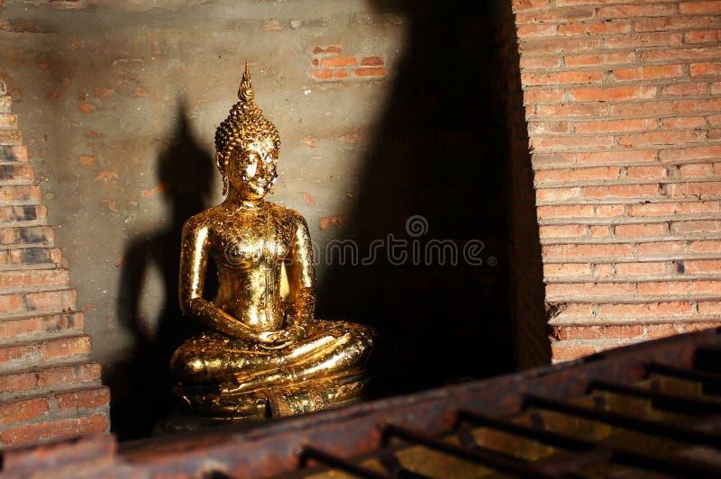 Escultura pequena da Buda com o oferecimento do phra dourado do wai das folhas em Ayutthaya, Tailândia fotografia de stock royalty free