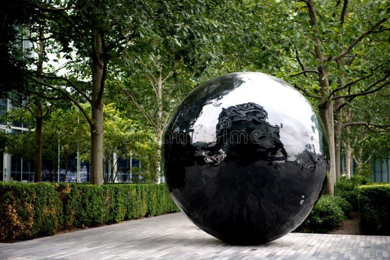 Escultura preta grande da esfera no banco do Th do rio imagem de stock royalty free