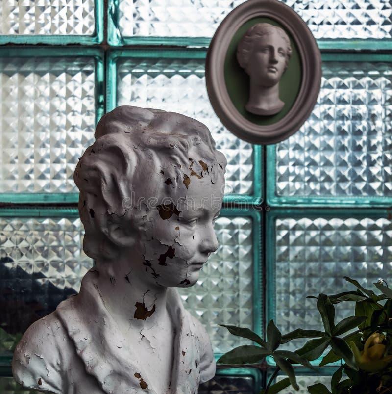 Escultura principal branca lascada contra a parede do bloco de vidro foto de stock