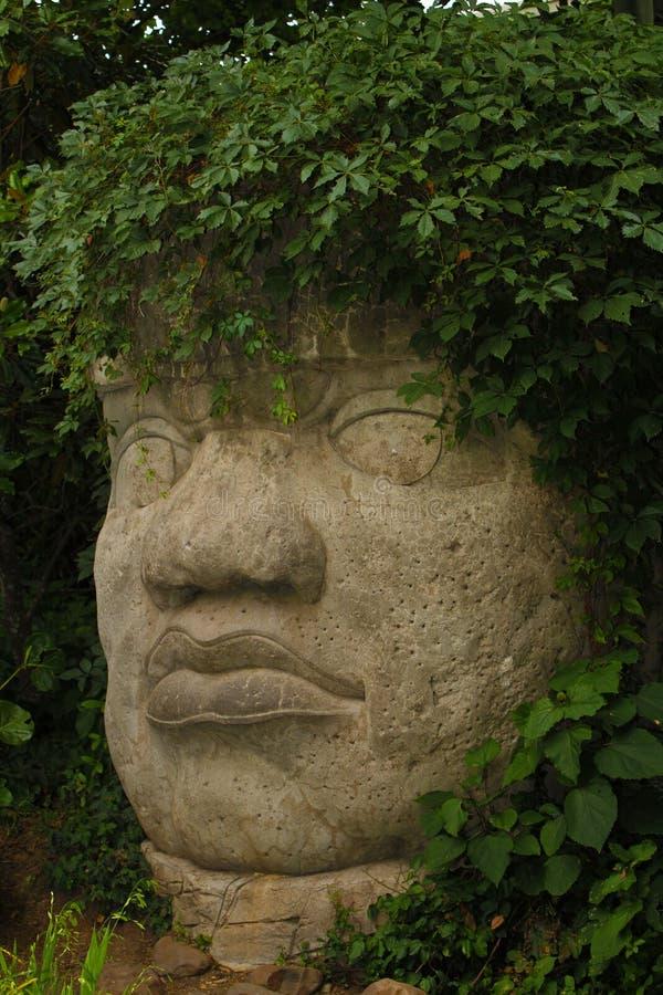 Escultura principal de piedra mesoamericana gigantesca con el pelo de la planta verde imagenes de archivo