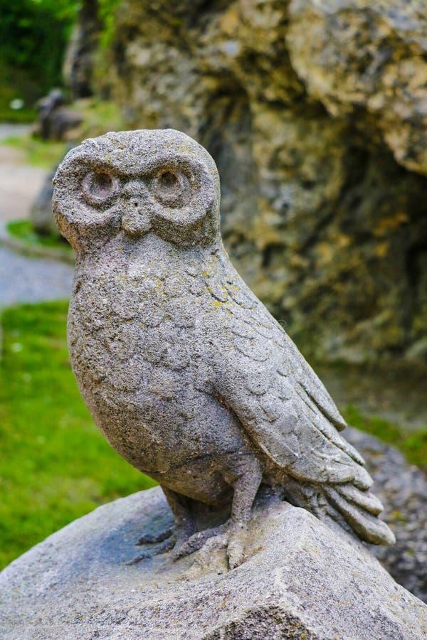 Escultura velha da coruja na pedra em um parque ou em um jardim fotos de stock royalty free