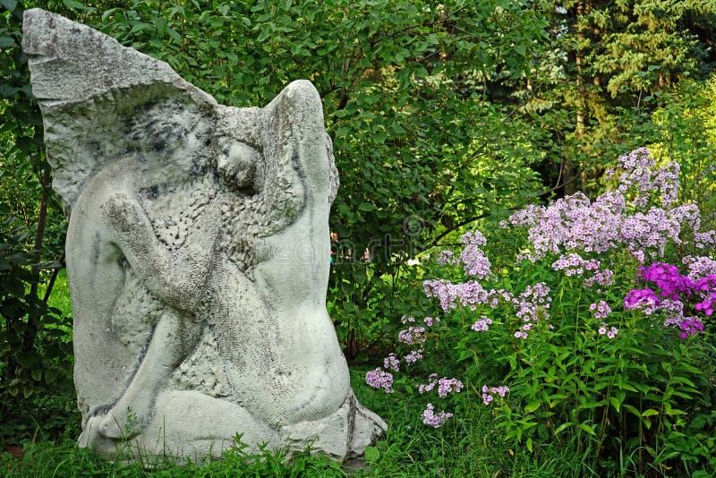 Escultura y flores del polemonio en el jardín de la ciudad imágenes de archivo libres de regalías