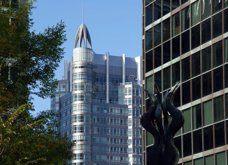 Escultura y rascacielos imagenes de archivo