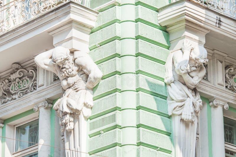 Esculturas de Atlantes na fachada da construção na rua de Ilinka imagens de stock
