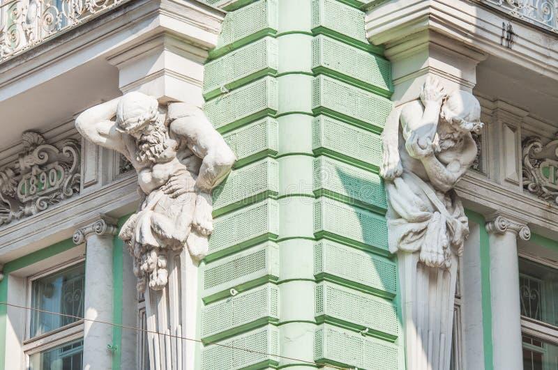Esculturas de Atlantes na fachada da construção na rua de Ilinka fotografia de stock