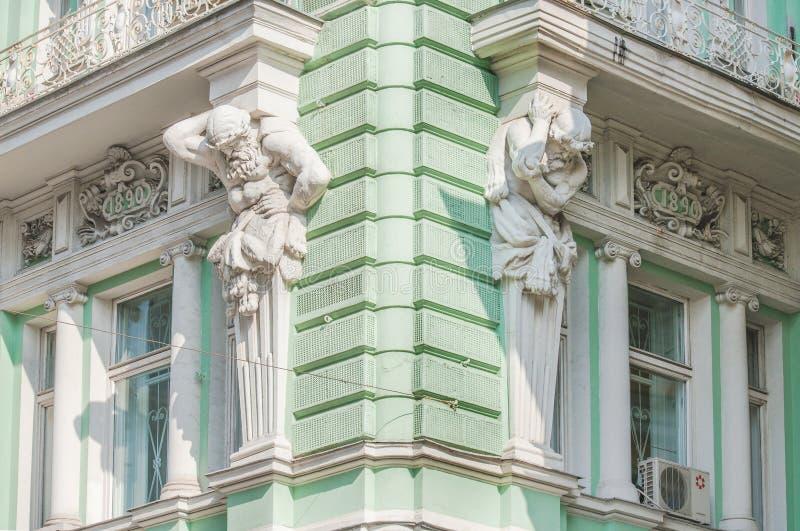 Esculturas de Atlantes na fachada da construção na rua de Ilinka fotografia de stock royalty free