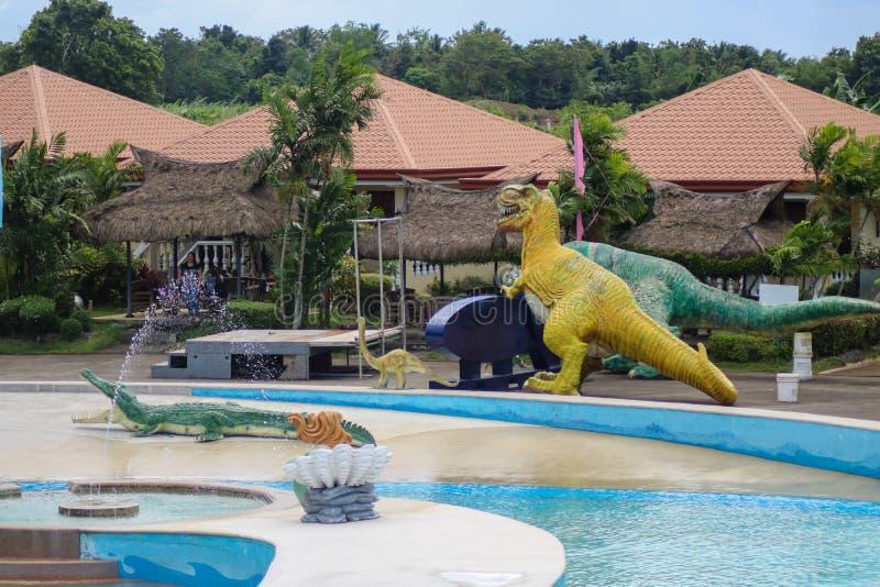 Esculturas do dinossauro perto de uma piscina nas Filipinas foto de stock royalty free