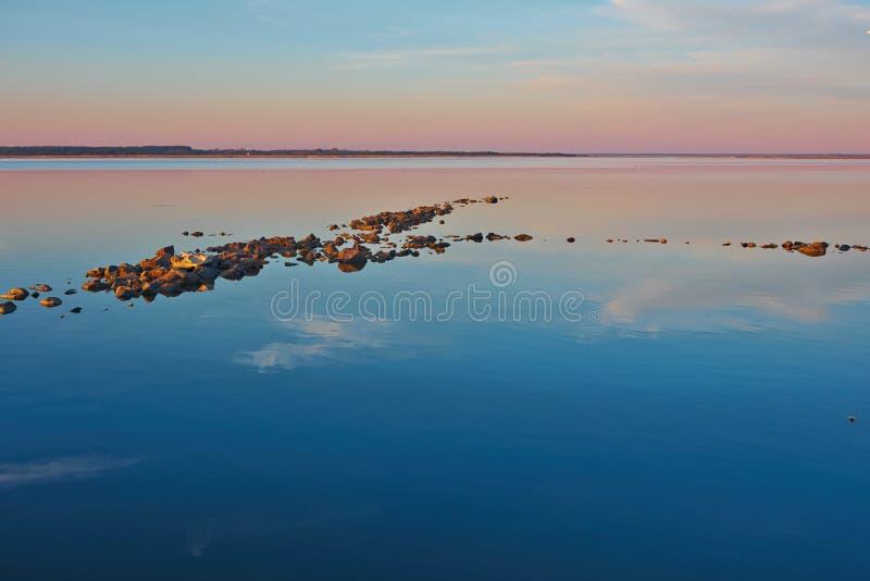 Escupitajo rocoso en un mar tranquilo fotos de archivo