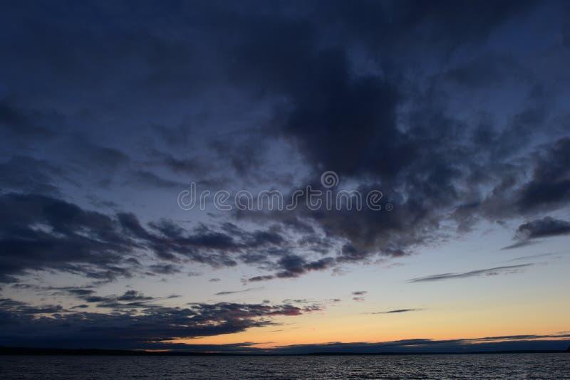 Escuridão e luz no céu crepuscular nas nuvens acima da água do lago imagem de stock