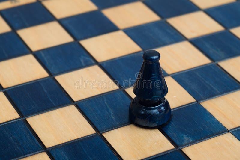 Escuro - bispo azul no tabuleiro de xadrez de madeira fotos de stock royalty free