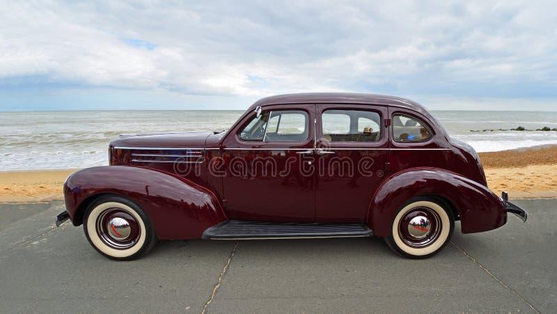 Escuro clássico - carro vermelho do motor de Studebaker estacionado na praia e no mar do passeio da frente marítima no fundo imagem de stock royalty free